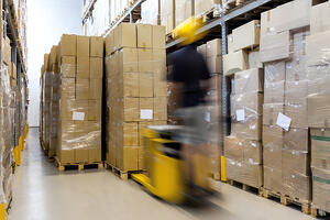 Fork lift with operator working in warehouse-1