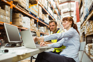 Warehouse worker and manager looking at laptop in a large warehouse-1